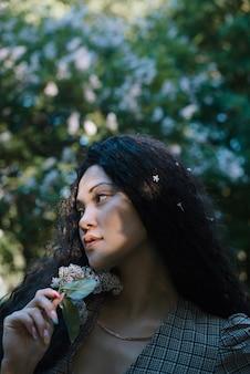 Красивая азиатская женщина, стоящая перед цветущими деревьями с цветами в руке
