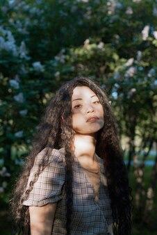 Красивая азиатская женщина, стоящая перед цветущими деревьями