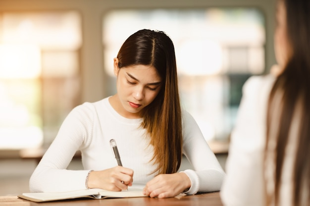 아름다운 아시아 여성 학생은 줄줄이 교육 라이프스타일 대학 대학에 앉아 있는 대학 교실 학생들의 시험을 위해 앉아 있습니다.