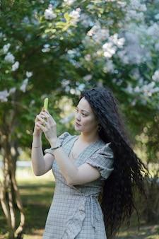 Красивая азиатская женщина фотографирует со своим смартфоном перед цветущими деревьями
