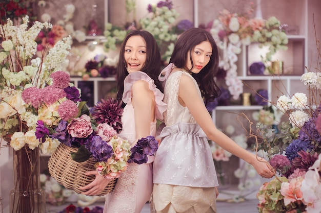 Beautiful asian florist girls holding bouquet and basket of flowers for sale against floral bokeh