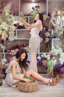 Beautiful asian florist girls making bouquet of flowers for sale against floral bokeh