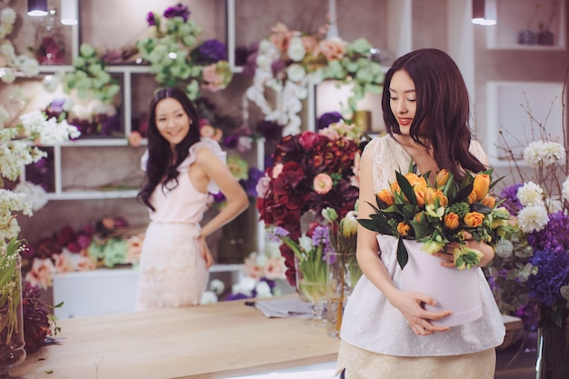 Beautiful asian florist girls making bouquet of flowers on table for sale against floral bokeh