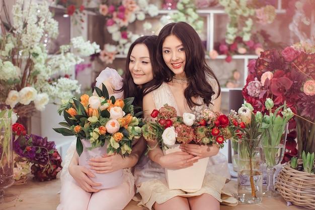 Красивые азиатские девушки флорист делают букет цветов на столе для продажи против цветочного боке