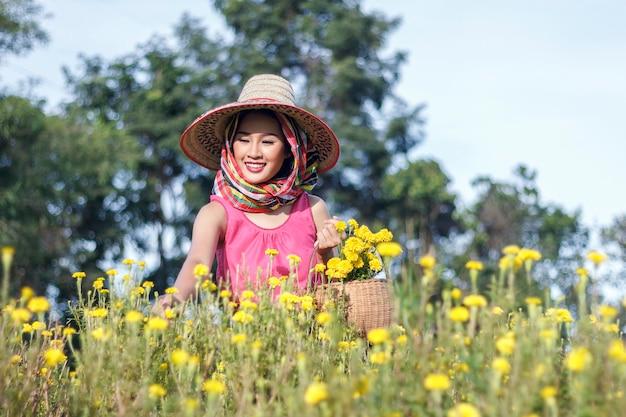 금 잔 화 꽃 필드에 아름 다운 아시아 정원사 여자