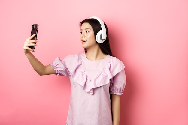 Beautiful asian girl blogger taking selfie in wireless headphones, make photo for social media on smartphone, standing in dress against pink background.