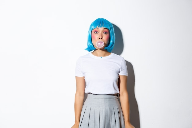 Beautiful asian girl in blue wig and schoolgirl costume, blowing bubble gym with silly face