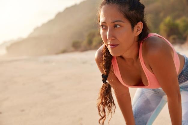 美しいアジアの女の子は、ジョギング運動の後に息をのむ