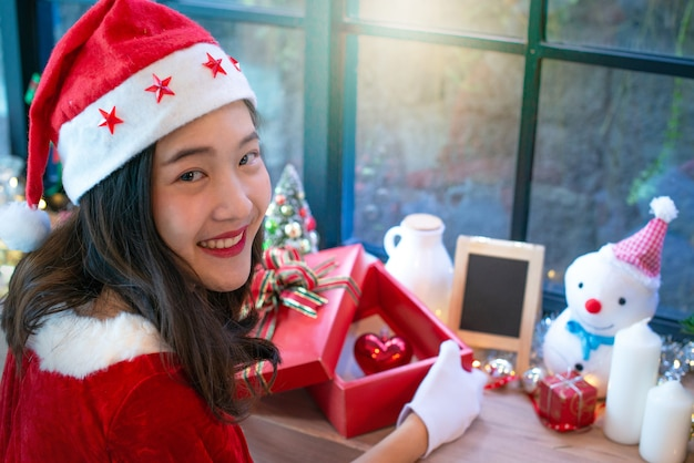 Beautiful asian girl in christmas wearing and santa hat, open gift box, red heart in box