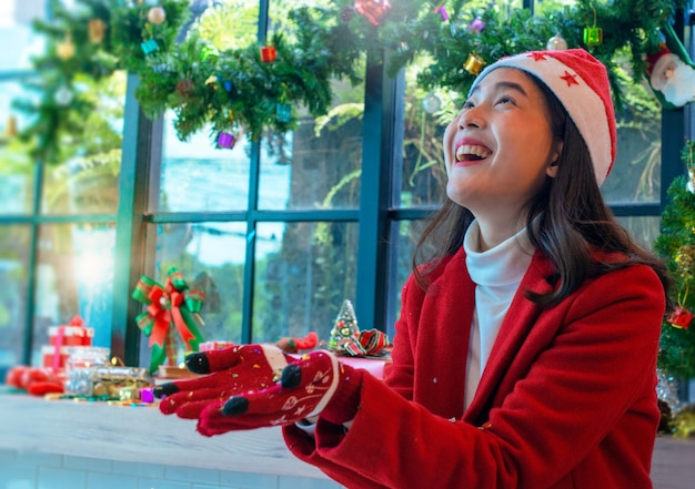 Beautiful asian girl in christmas wearing and santa hat, with two hand holding or offering something