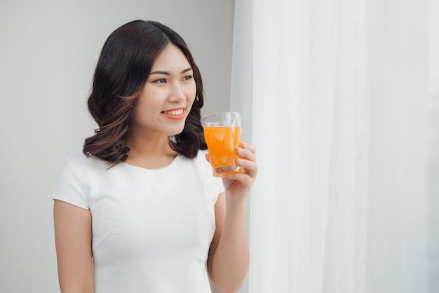 オレンジジュースのガラスを飲む美しいアジアの女の子。