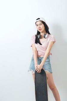 Beautiful asian girl holding skateboard