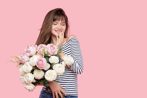 美しいアジアの少女は、明るい背景に彼女の手で美しい緑豊かな花束を保持しています。