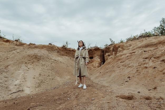 暗い秋の日に砂の採石場の前でポーズをとるベージュのトレンチコートを着た美しいアジアの女の子。水平方向の画像。