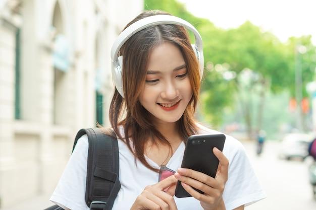 아름다운 아시아 소녀가 휴대전화로 음악을 듣고 있다