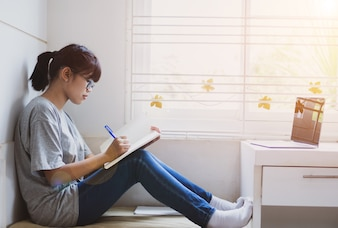 Beautiful Asian girl learning and writing in notebook or homework, sitting short notes