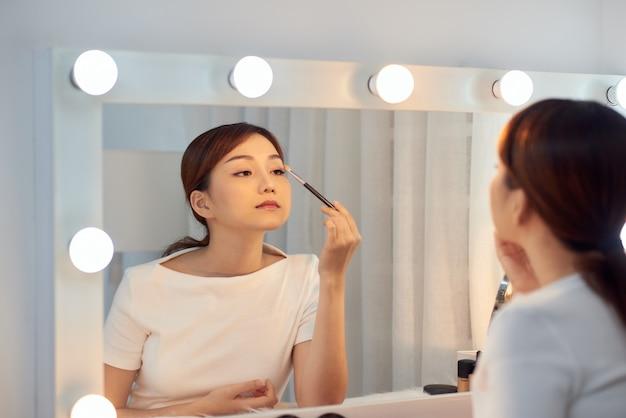 鏡を見て、ブラシで化粧品を適用する美しいアジアの女の子