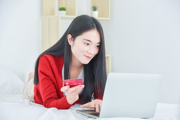 Beautiful asian girl lying on bed while surfing web on laptop computer and holding credit card trying to buy goods online