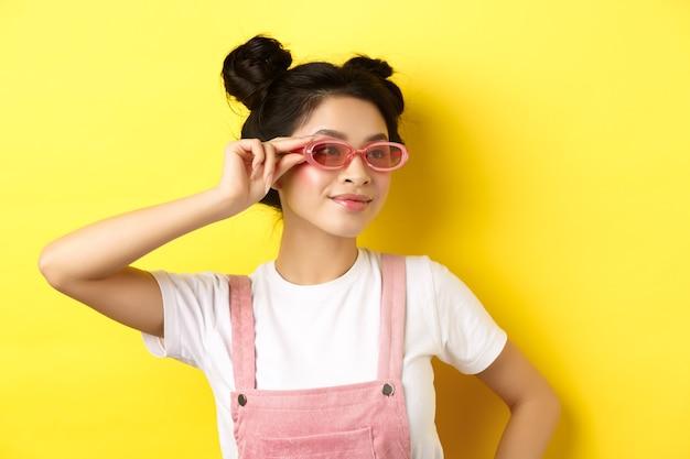 아름 다운 아시아 여자 세련 된 선글라스에 넣어 웃 고, 유행 여름 옷을 입고, 노란색에 서.
