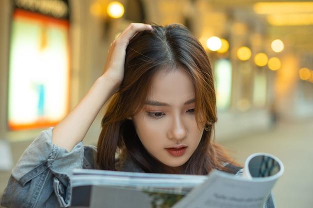 通りで雑誌を読んで美しいアジアの女の子