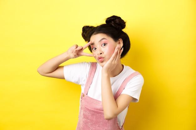 아름 다운 아시아 여자 v 기호를 표시 하 고 귀여운 pouting, 화장과 바보 같은 얼굴, 노란색에 서.