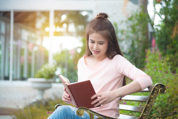 Beautiful asian girl sitting on bench reading book in park