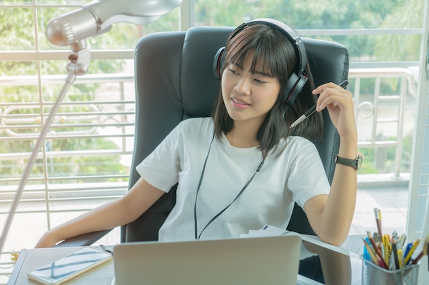 Beautiful asian girl sitting smile seem so happy to listening music on headphones with her
