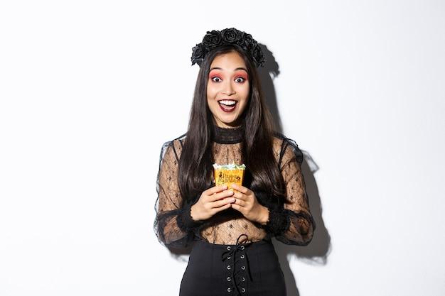 Bella ragazza asiatica che sorride felice, che tiene i dolci, che porta il costume della strega su halloween, che gode del dolcetto o del trattamento.