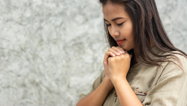 Beautiful asian girl standing praying for god's blessing.