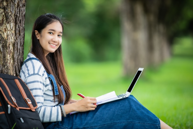 Beautiful asian girl student holding books and smiling and learning and education concept  on park in summer for relax time
