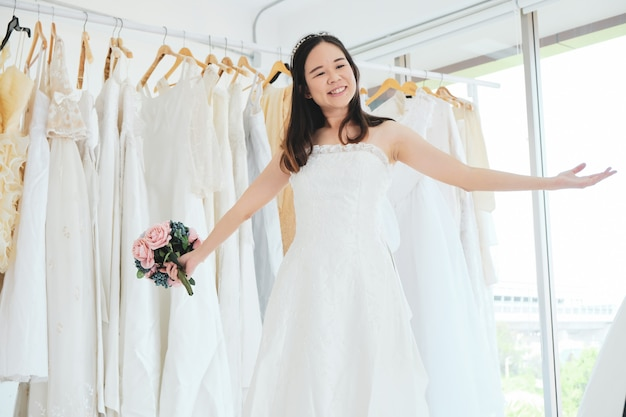 Beautiful asian girl try bridal dress in the shop.