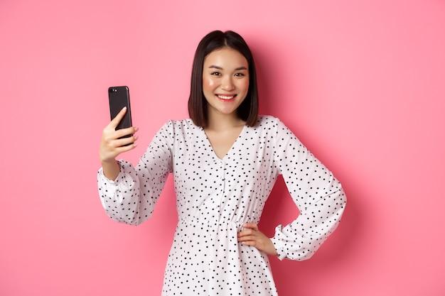 Красивая азиатская девушка, использующая приложение для фотофильтров и делающая селфи на мобильном телефоне, позирует в милом платье на розовом фоне.