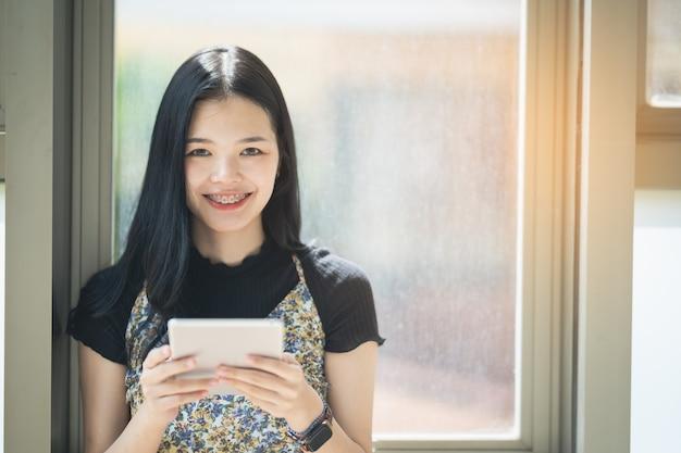 タブレットと笑顔、ライフスタイルビジネスコンセプトを使用して美しいアジアの女の子