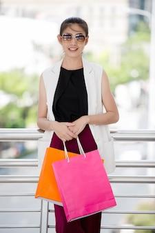 Красивая азиатская девушка гуляя и ходя по магазинам в городской улице города