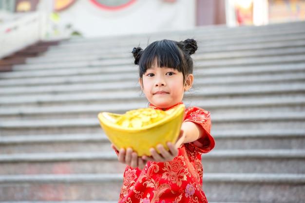 Красивая азиатская девушка носит красный чонсам и держит китайский золотой слиток перед мраморными ступенями красивого китайского храма на китайский новый год