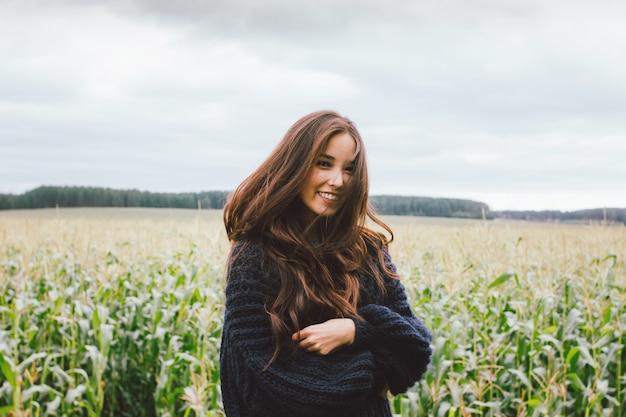 Beautiful asian girl wearing knitted sweater in autumn corn field.