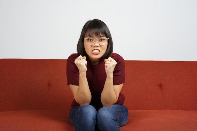 赤いシャツとブルージーンズを身に着けている美しいアジアの女の子赤いソファに座って怒っているジェスチャーを取得します