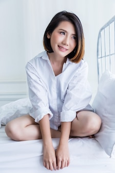 Beautiful asian girl white white shirt ralax on white bed next to window curtian