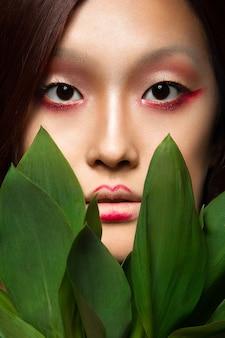 Красивая азиатская девушка с ярким искусством макияжа в зеленых листьях.