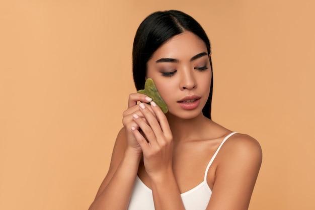 Beautiful asian girl with beauty gua sha quartz stone for massage on beige