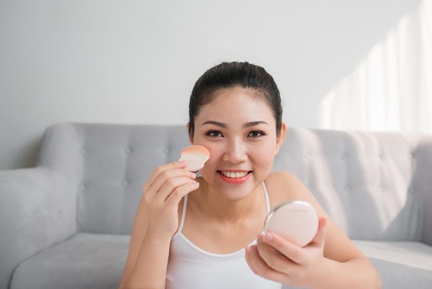 화장용 파우더 브러시를 가진 아름다운 아시아 소녀. 메이크업 컨셉