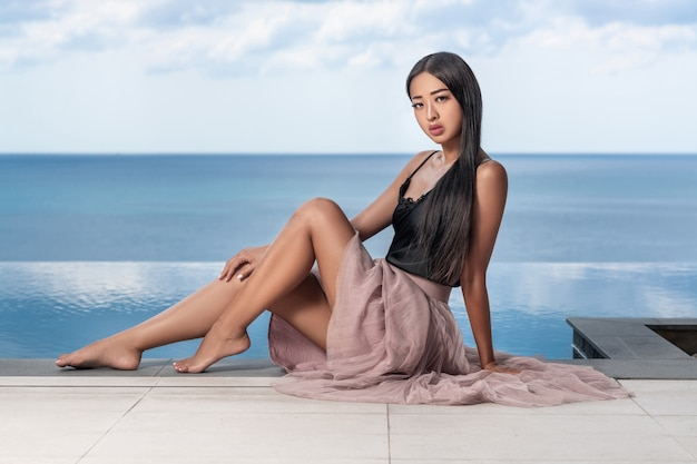 Beautiful asian girl with long hair posing on the edge of the infinity pool. fashion and style on a tropical vacation