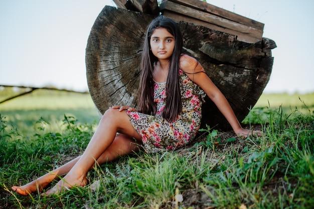 Красивая азиатская девушка с длинными волосами сидит на траве возле большого пня бревенчатой хижины