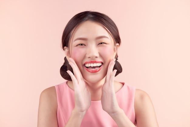 전문 메이크업과 핑크에 고립 된 세련 된 헤어 스타일으로 아름 다운 아시아 여자. 화장품 및 메이크업