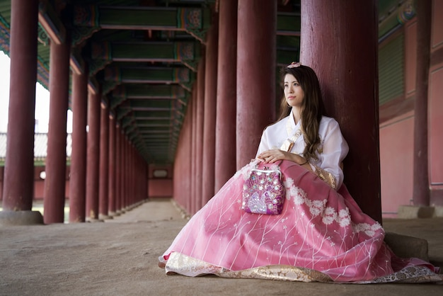Beautiful asian girl with south korea traditional hanbok style dress sitting with smile