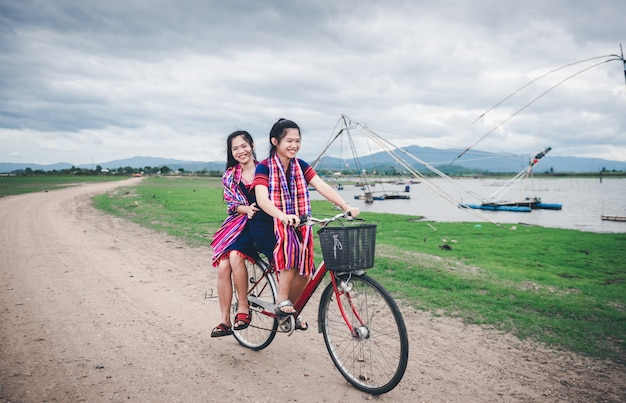 Beautiful asian girls enjoy travel at countryside of thailand by riding on bicycle