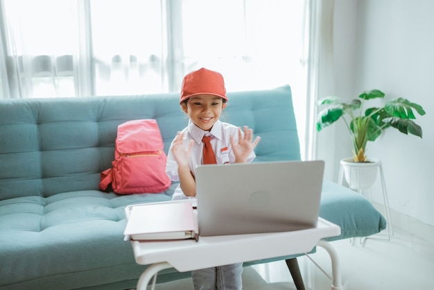 Beautiful asian indonesian primary school student with uniform waving to her teacher and friend during online class session at home