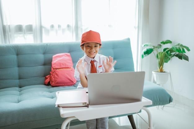 自宅でのオンラインクラスセッション中に彼女の先生と友人に制服を振っている美しいアジアのインドネシアの小学生