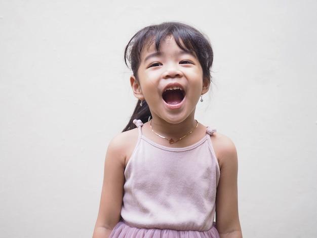 Красивая азиатская девушка ребенка из индонезии показывает выражение счастья с открытым ртом. изолированные на белом