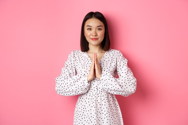 Beautiful asian lady in dress asking for help, holding hands in pray or namaste gesture, thanking you, standing over pink.